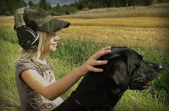 Flicka med labrador under jakt.